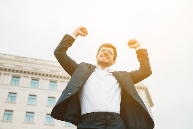 Glimlachend portret van een vrolijke jonge zakenman balde zijn vuist Gratis Foto