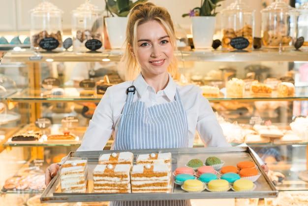 Glimlachend portret van een vrouwelijke bakker die groot dienblad met kleurrijke makarons en gebakjes houdt Gratis Foto