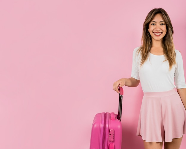 Glimlachend portret van jonge vrouw die zich met haar bagagezak tegen roze achtergrond bevinden Gratis Foto