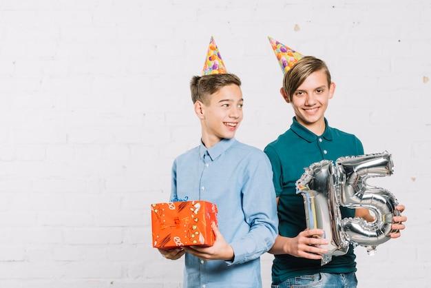 Glimlachend portret van twee jongens die partijhoed op de doos van de hoofdholdingsgift en nummer 15 folieballon dragen Gratis Foto