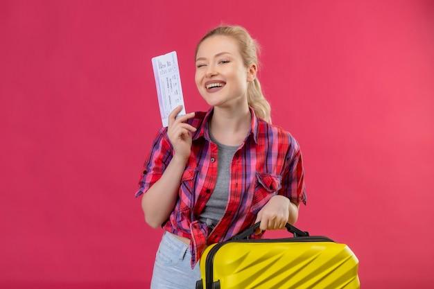 Glimlachend reizigers jong meisje die de rode koffer en het kaartje van de overhemdsholding op geïsoleerde roze achtergrond dragen Gratis Foto