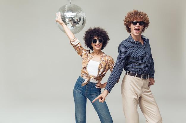 Glimlachend retro houdend van paar dichtbij discobal. Gratis Foto