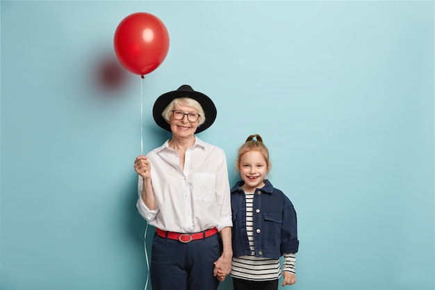 Glimlachend roodharig meisje komt oma feliciteren met moederdag, draagt een gestreepte trui en een spijkerjasje. blij dat senior dame in stijlvolle zwarte hoed, ballon draagt, hand houdt van kleine kleindochter Gratis Foto