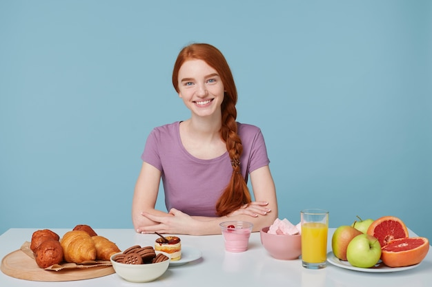 Glimlachend roodharig meisje met gevlochten haar zittend aan een tafel, op het punt om te ontbijten kijkend naar de camera, geïsoleerd op blauwe muur Gratis Foto
