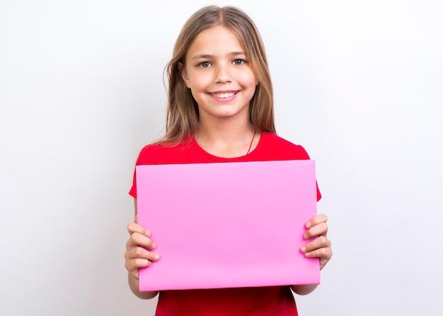 Glimlachend schoolmeisje dat leeg voorbeeldenboek toont Gratis Foto