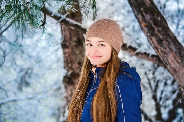Glimlachend tienermeisje in een blauw donsjack en een bruine hoed op een de winterachtergrond van sneeuwspartakken Premium Foto