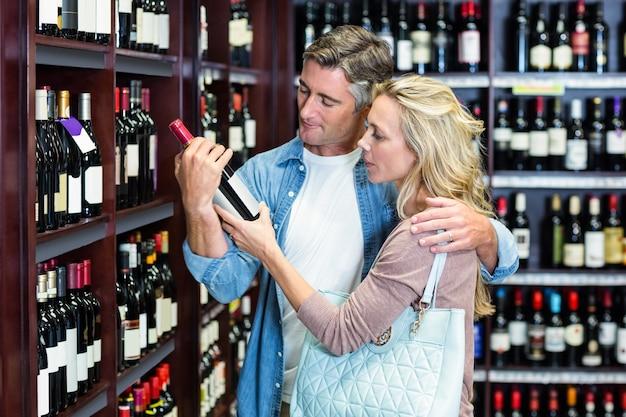 Glimlachend toevallig paar dat wijnfles bekijkt Premium Foto