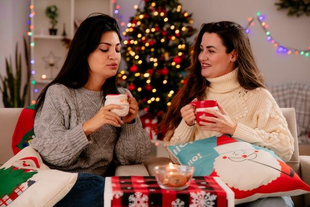 Glimlachend vrij jong meisje houdt beker vast en kijkt naar haar tevreden vriend houdt beker zittend op fauteuils met gesloten ogen en geniet van kersttijd thuis Gratis Foto