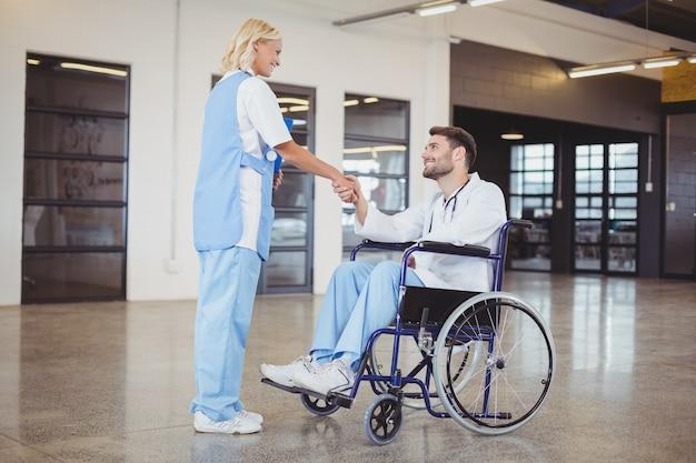 Glimlachend vrouwelijk artsenhandenschudden met artsenzitting op rolstoel Premium Foto