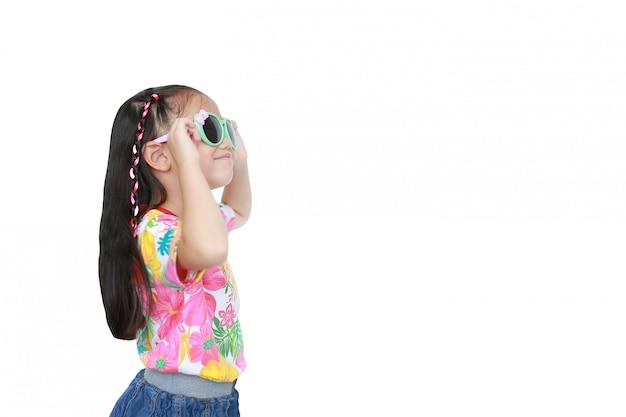 Glimlachend weinig aziatisch kindmeisje die een bloemenpatroonzomerkleding en zonnebril dragen Premium Foto