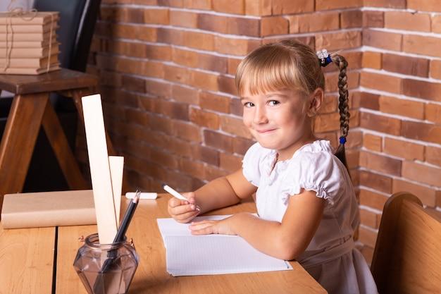 Glimlachend weinig studentenmeisje, zittend aan een schoolbank. het kind maakt huiswerk. voorschoolse educatie. Premium Foto