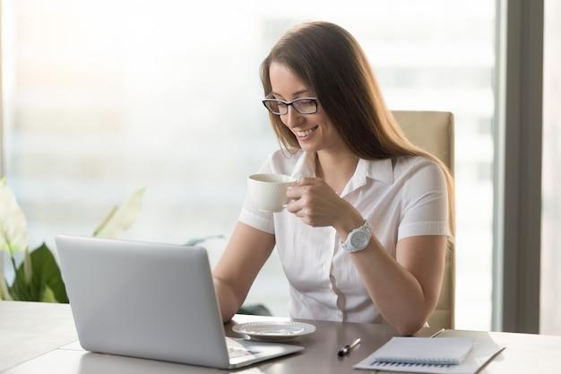 Glimlachende aantrekkelijke onderneemster die het stimuleren koffie tijdens onderbreking op het werk drinkt Gratis Foto
