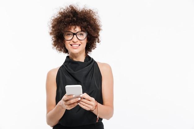 Glimlachende aantrekkelijke onderneemster die in oogglazen mobiele telefoon houdt Gratis Foto