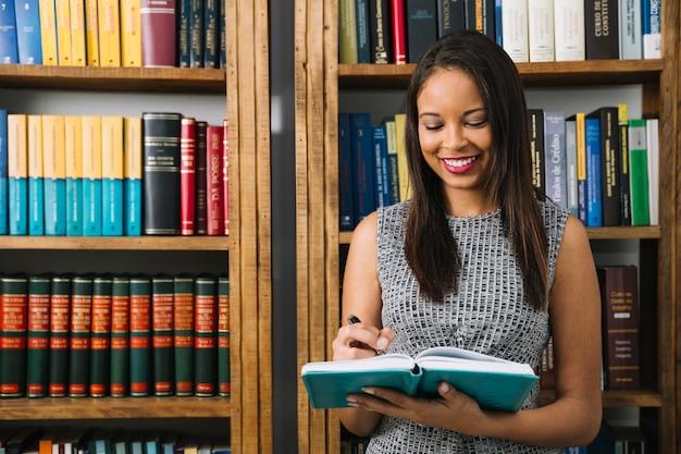 Glimlachende afrikaanse amerikaanse jonge dame met boek Gratis Foto