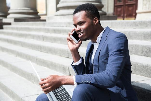 Glimlachende afrikaanse jonge zakenman die op mobiele telefoonzitting op trap met laptop spreekt Gratis Foto