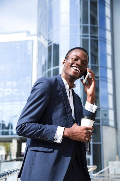 Glimlachende afrikaanse jonge zakenman voor de collectieve bouw die op mobiele telefoon spreekt Gratis Foto