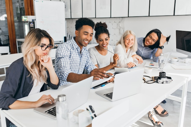 Glimlachende afrikaanse student die met potlood op laptop scherm richt. geconcentreerde blonde vrouw in glazen die kin met hand steunen tijdens het werken met computer in bureau. Gratis Foto