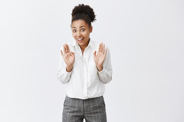 Glimlachende afro-amerikaanse vrouw handen opsteken in overgave, iets tegenhouden Gratis Foto