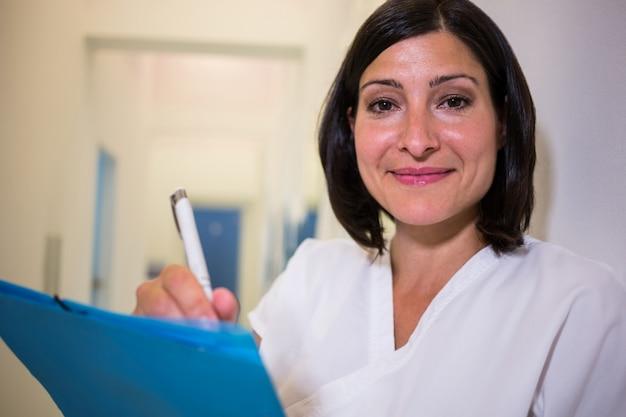 Glimlachende arts die patiëntenrapport onderzoekt Gratis Foto