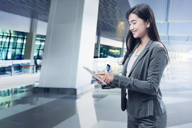 Glimlachende aziatische bedrijfsvrouw die digitale tablet gebruiken Premium Foto