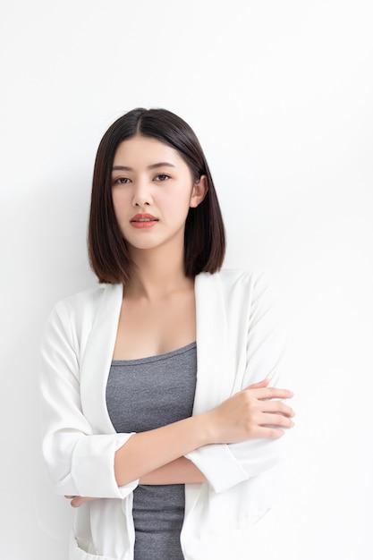 Glimlachende aziatische bedrijfsvrouw die en zich de camera bevindt bekijkt Premium Foto