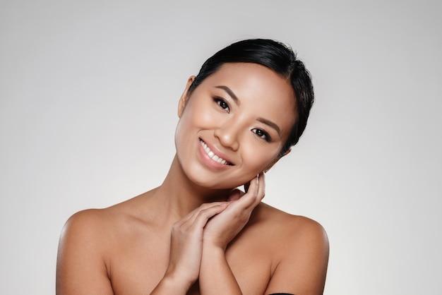 Glimlachende aziatische dame wat betreft haar duidelijke huid Gratis Foto