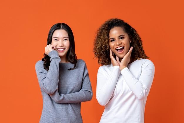 Glimlachende aziatische en afrikaanse amerikaanse vrouwenvrienden in verrast gebaar Premium Foto