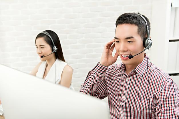 Glimlachende aziatische mannelijke telemarketing klantenserviceagent die in call centre werkt Premium Foto