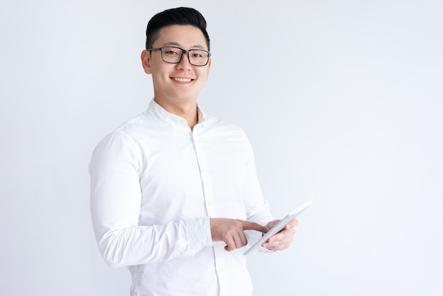 Glimlachende aziatische mens die tabletcomputer met behulp van Gratis Foto
