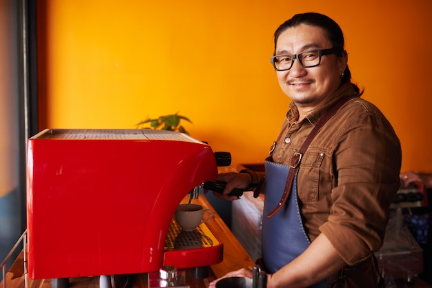 Glimlachende aziatische mens op middelbare leeftijd in schort die zich naast espressomachine en het glimlachen bevinden Gratis Foto