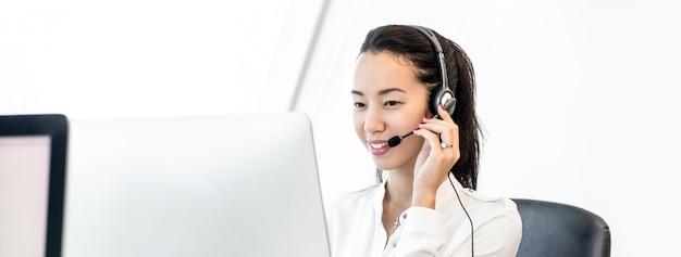 Glimlachende aziatische mooie vriendschappelijke vrouw op de achtergrond van de call centrebanner Premium Foto
