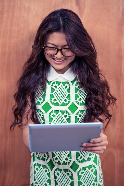 Glimlachende aziatische vrouw die tablet gebruiken tegen houten muur Premium Foto