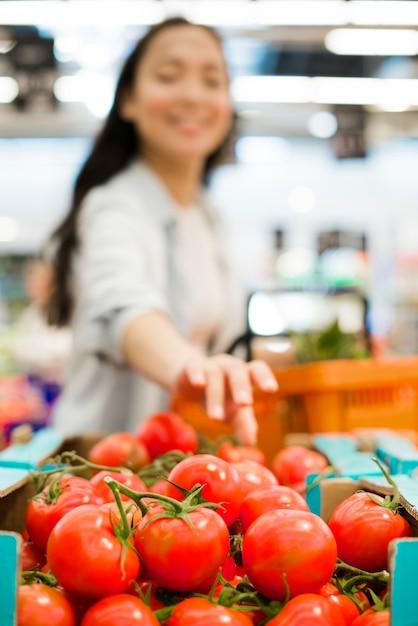 Glimlachende aziatische vrouw die tomaten in supermarkt kiezen Gratis Foto