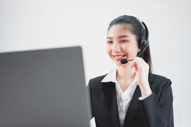 Glimlachende aziatische vrouwenadviseur die microfoonhoofdtelefoon van de exploitant van de klantenondersteuningstelefoon dragen op het werk. Premium Foto