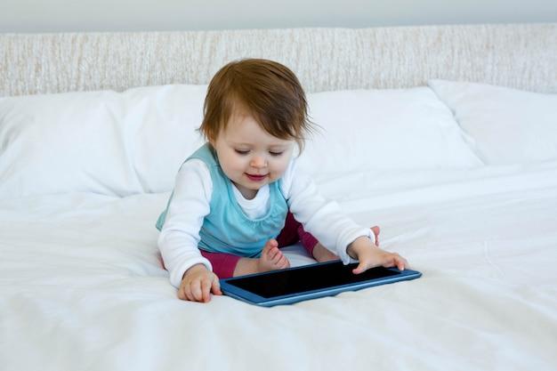 Glimlachende baby spelen met een tablet op een bed Premium Foto