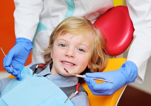 Glimlachende babyjongen met blond krullend haar als tandvoorzitter. Premium Foto