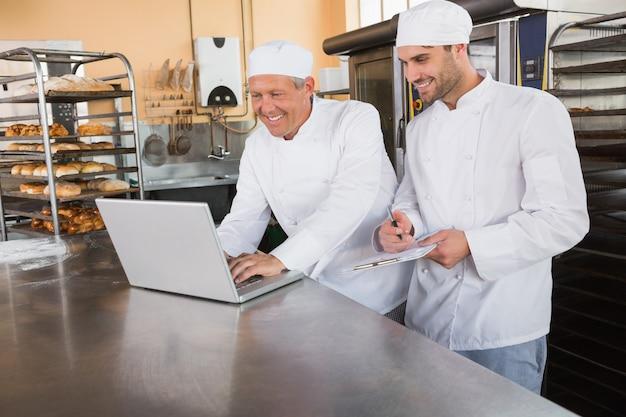 Glimlachende bakkers die aan laptop samenwerken Premium Foto