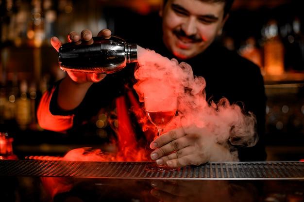 Glimlachende barman met snorren die een rook in het cocktailglas gieten van de schudbeker Premium Foto