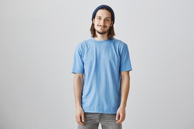 Glimlachende bebaarde jonge man in blauw t-shirt en muts op zoek enthousiast Gratis Foto
