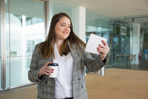 Glimlachende bedrijfsvrouwenholdingstablet en drank in openlucht Gratis Foto
