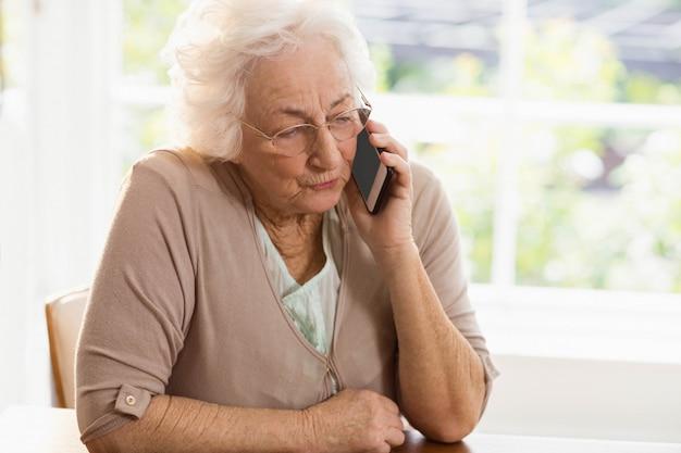 Glimlachende bejaarde telefoon die thuis roept Premium Foto