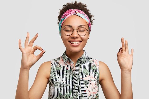 Glimlachende blije jonge vrouw student tevreden met resultaten van geslaagd examen, toont goed teken, glimlacht oprecht Gratis Foto