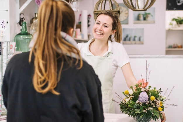 Glimlachende bloemist die met cliënt spreekt Gratis Foto