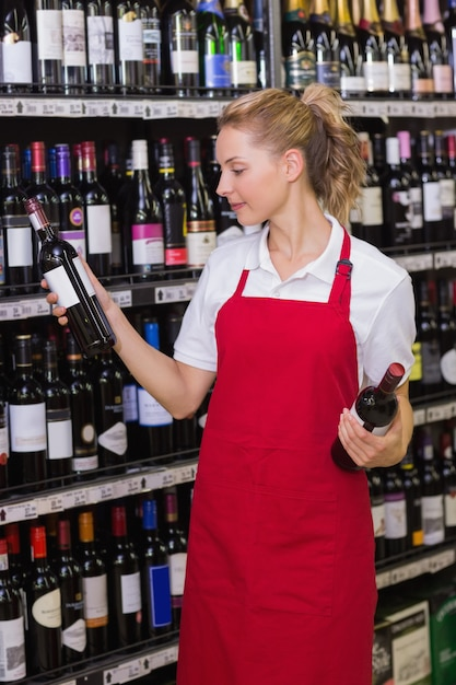 Glimlachende blonde arbeider die een wijnfles bekijkt Premium Foto