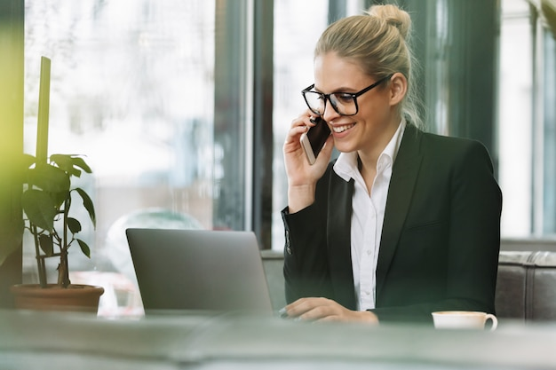 Glimlachende blonde bedrijfsvrouw die door mobiele telefoon spreekt Gratis Foto