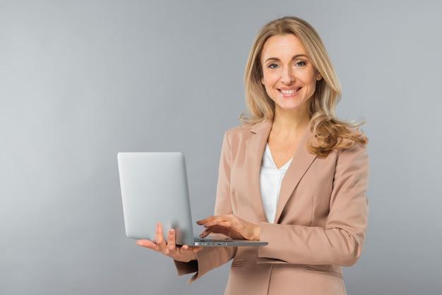Glimlachende blonde jonge onderneemster die laptop met behulp van ter beschikking tegen grijze achtergrond Gratis Foto