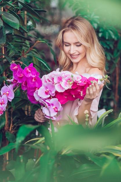Glimlachende blonde jonge vrouw die zich voor groene installaties bevinden die exotische roze orchideebloemen bekijken Gratis Foto
