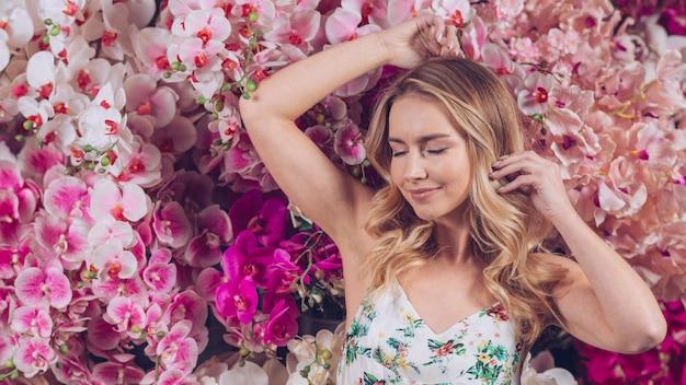 Glimlachende blonde jonge vrouw met gesloten oog status tegen kleurrijke orchideeën Gratis Foto