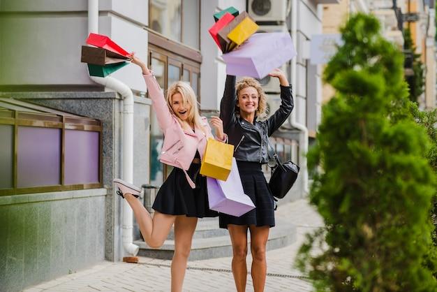 Glimlachende blonde meisjes met boodschappentassen staan Gratis Foto
