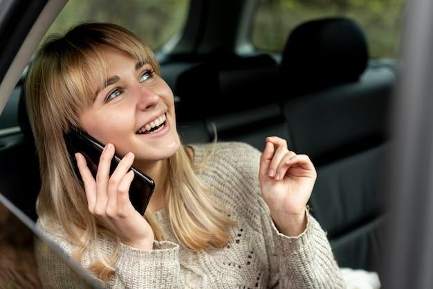 Glimlachende blondevrouw die op telefoon spreken Gratis Foto